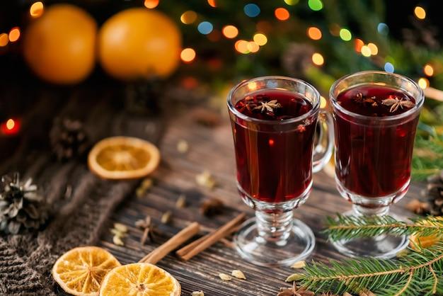 Vin chaud dans des verres en verre avec orange, cannelle, cardamome, une étoile d'anis sur la table décorée avec un sapin de noël et une guirlande