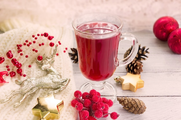 Vin chaud et décoration de noël - cerf doré, fruits rouges, cônes, étoiles sur table en bois blanc