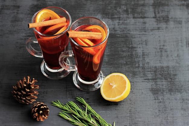 Vin chaud doux pour deux personnes dans des verres, des cônes de sapin décorés et du romarin.