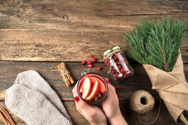 Vin chaud entre les mains d'une femme, bouquet de branches de pin et mitaines.