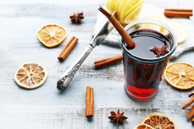 Vin chaud et épices savoureux, sur fond de bois bleu, gros plan