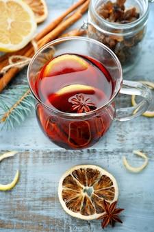 Vin chaud et épices savoureux, sur une surface en bois bleue, gros plan