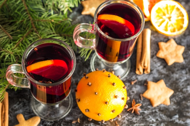 Vin chaud de noël avec des biscuits au gingembre orange anis cannelle et sapin sur la table sombre