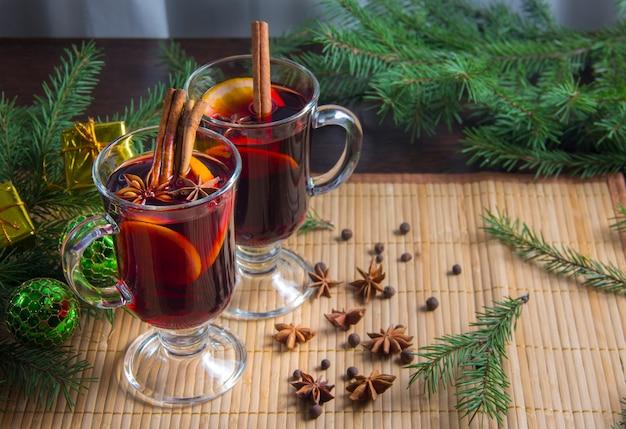 Vin chaud de noël à la cannelle et à l'orange. sur la table sont des brindilles d'épinette et des jouets