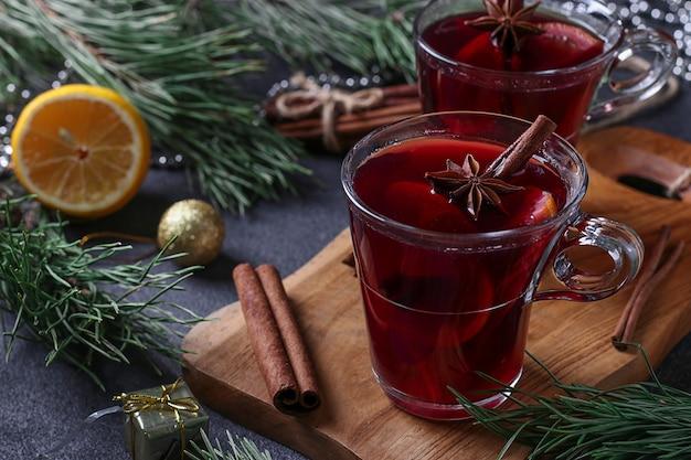 Vin chaud de noël dans deux tasses en verre sur une planche en bois sur fond sombre, gros plan