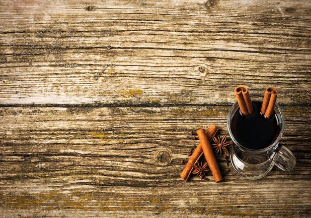 Vin chaud de noël dans une tasse en verre sur une table en bois.