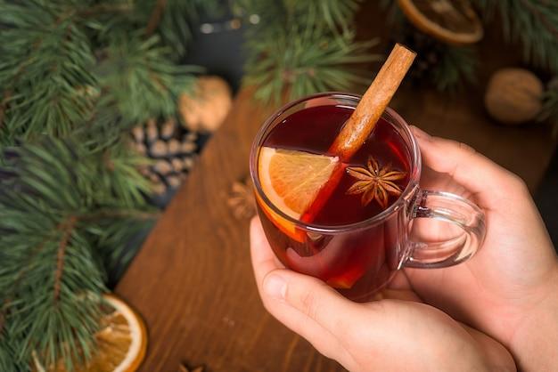 Vin chaud de noël dans un verre entre les mains d'un homme avec des tranches d'orange à base de vin rouge avec des bâtons de cannelle épicés