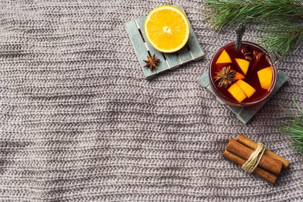 Vin chaud de noël avec des épices et des fruits sur une couverture tricotée.