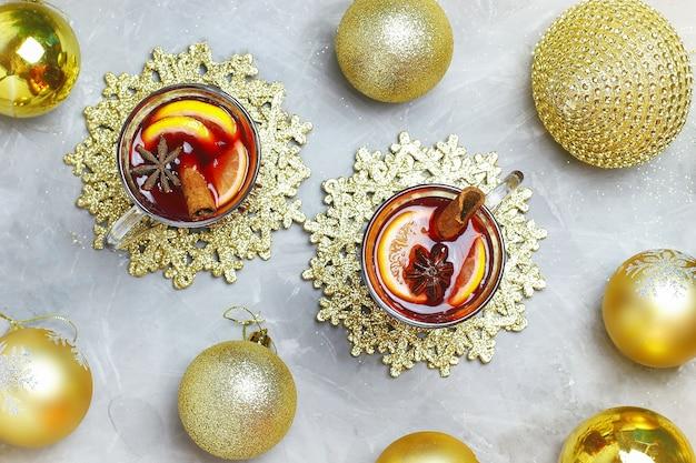 Vin chaud de noël avec des épices et des tranches de citron sur du béton gris avec un décor doré de noël