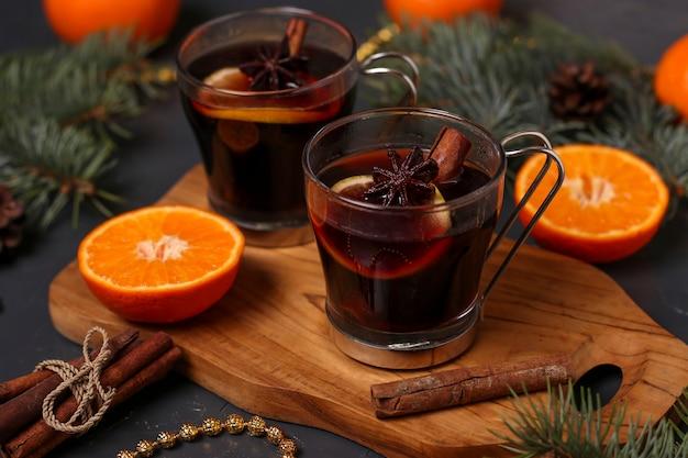Vin chaud de noël et mandarines sur fond sombre, gros plan, orientation horizontale