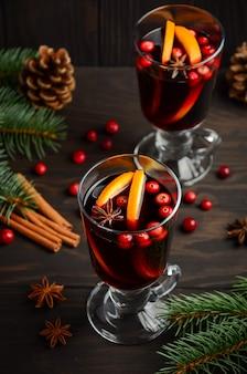 Vin chaud de noël à l'orange et aux canneberges. concept de vacances décoré de branches de sapin et d'épices.