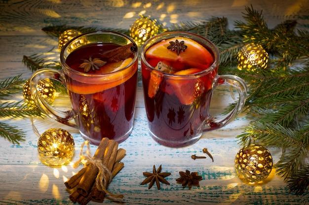 Vin chaud à l'orange, à l'anis et à la cannelle sur fond de branches d'arbres de noël et guirlande. boisson de noël réchauffante.