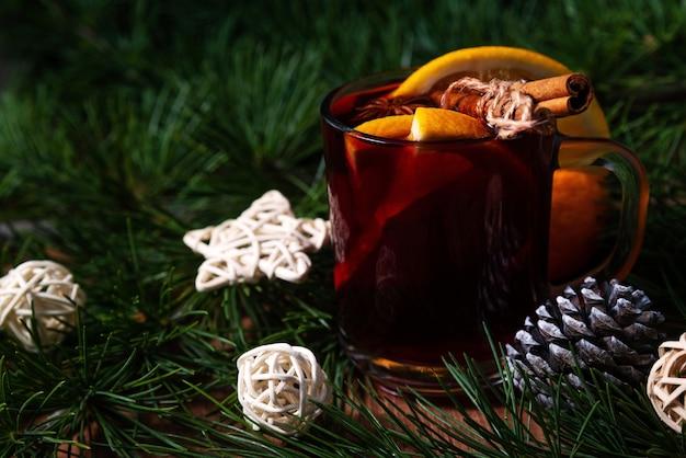 Vin chaud parfumé dans des tasses en verre sur fond de vacances de noël.
