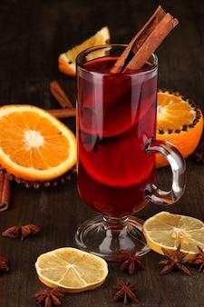 Vin chaud parfumé en verre avec des épices et des oranges autour sur une table en bois