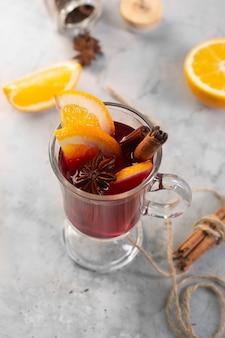 Vin chaud avec tranche d'orange et d'épices sur fond de béton gris