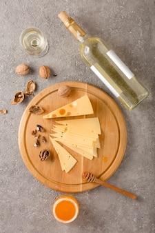 Vin et collations. fromage, noix et miel sur un fond de béton gris.