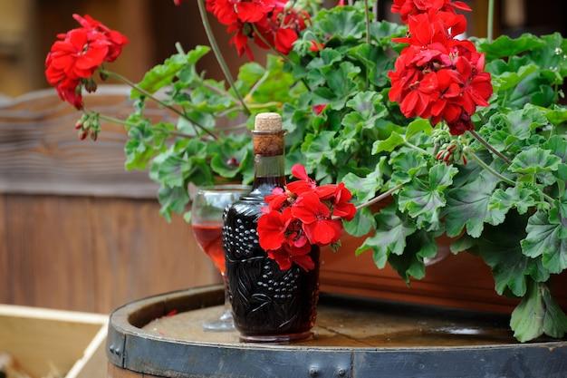 Vin dans de vieilles bouteilles dans un tonneau décoré de fleurs