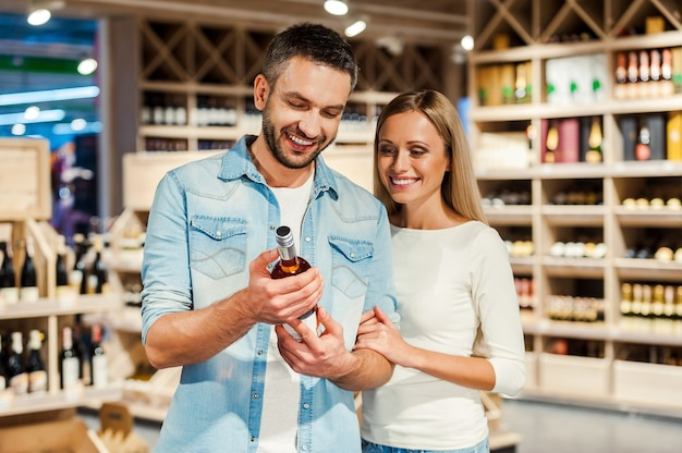 Ce vin doit être excellent. heureux jeune couple choisissant du vin et souriant en se tenant debout dans un magasin de vin