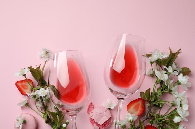 Vin, macarons, fraise et fleurs sur fond rose