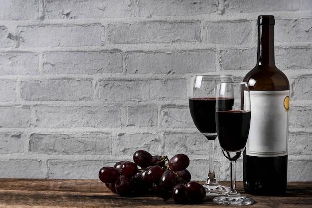 Vin et raisin sur fond de briques blanches de table en bois
