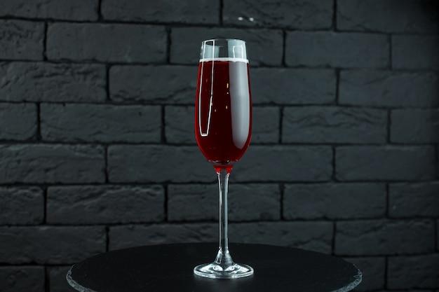 Vin de raisin semi-sucré rouge naturellement savoureux dans un élégant gobelet en verre se dresse sur une table en bois dans un restaurant. un excellent ajout au dîner
