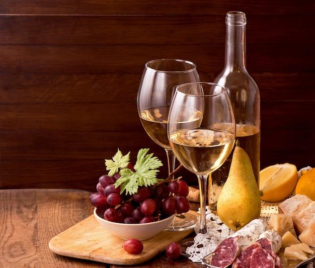 Vin et raisins dans un cadre vintage sur table en bois