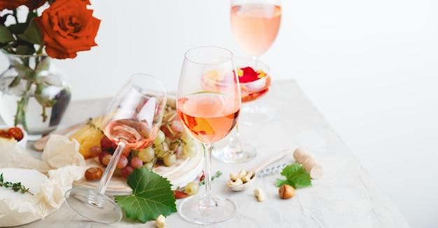 Vin rose dans différentes bouteilles de verres à vin sur une table blanche avec du fromage aux raisins, des collations bouquet de fleurs. composition moderne de vin rose de nature morte sur une surface en béton gris clair.
