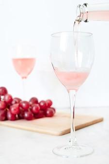 Le vin rosé est versé dans un verre à partir d'une bouteille.