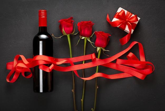 Vin, roses et coffret cadeau avec un arc rouge. concept d'amour
