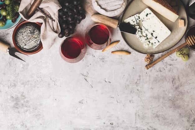 Vin rouge avec assortiment de charcuterie sur fond de béton rustique