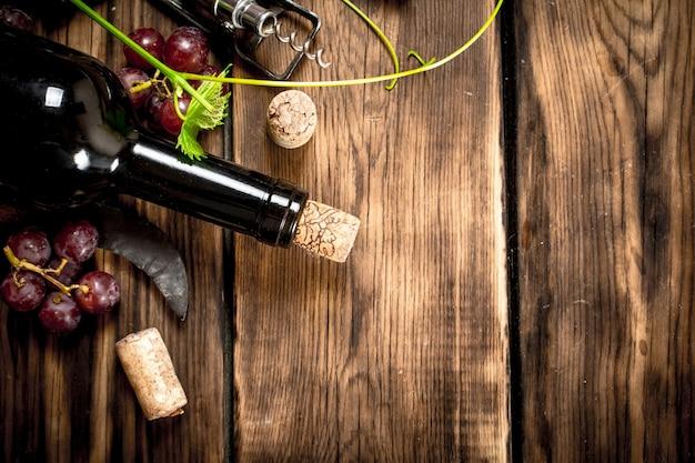 Vin rouge avec une branche de vigne sur table en bois.