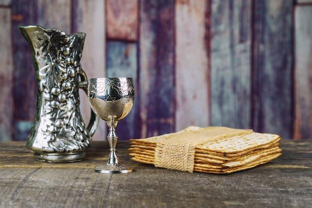 Vin rouge casher avec une assiette blanche de matza ou matza et une haggadah de pâque