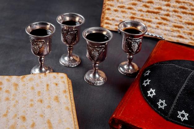 Vin rouge casher quatre de matzah ou matza haggadah de pâque sur un fond en bois vintage