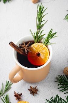 Vin rouge chaud aux épices avec branches de sapin et mandarines