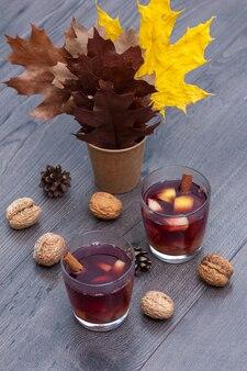 Vin rouge chaud aux épices et fruits sur une table en bois. feuilles d'automne