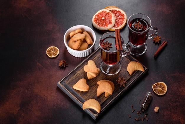 Vin rouge chaud de noël aux épices et fruits sur une table sombre. boisson chaude traditionnelle au moment de noël