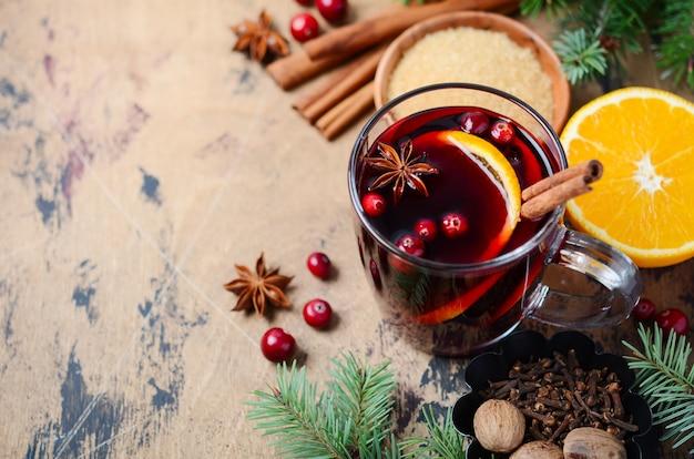 Vin rouge chaud de noël avec orange, canneberges et épices. vacances .