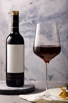 Vin rouge dans un verre et une bouteille sur la table.