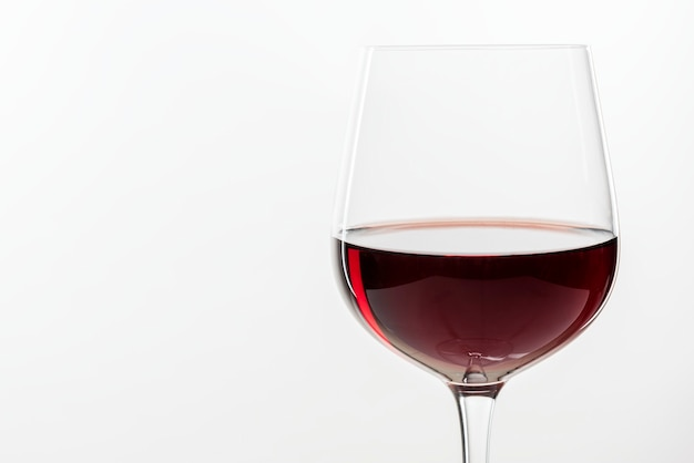 Vin rouge dans un verre sur fond blanc