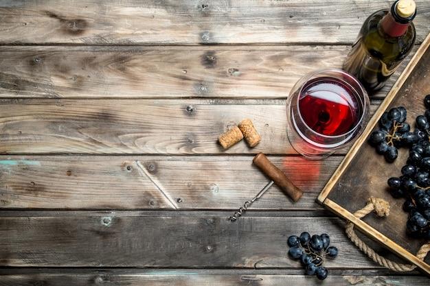 Vin rouge dans un verre avec des raisins et un tire-bouchon. sur un fond en bois.