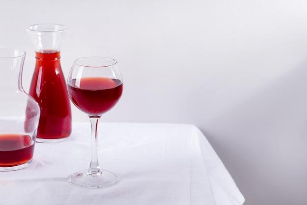 Vin rouge dans un verre à vin, une carafe et une bouteille avec des ombres isolées