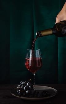 Le vin rouge est versé d'une bouteille dans un verre en verre et des raisins sur une assiette. fond de tissu vert.