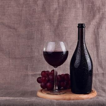 Vin rouge, fromages et raisins dans une configuration nature morte.