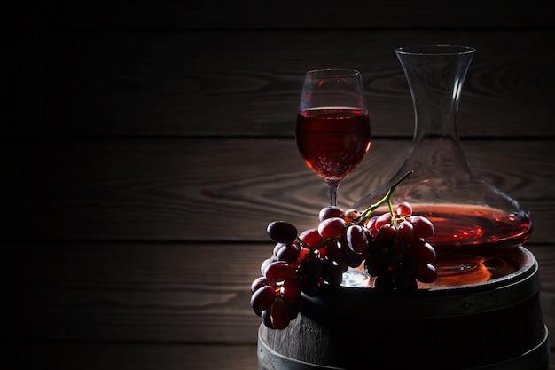 Vin rouge et grappe de raisin sur tonneau