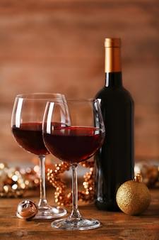 Vin rouge et ornements de noël sur table en bois sur fond de bois