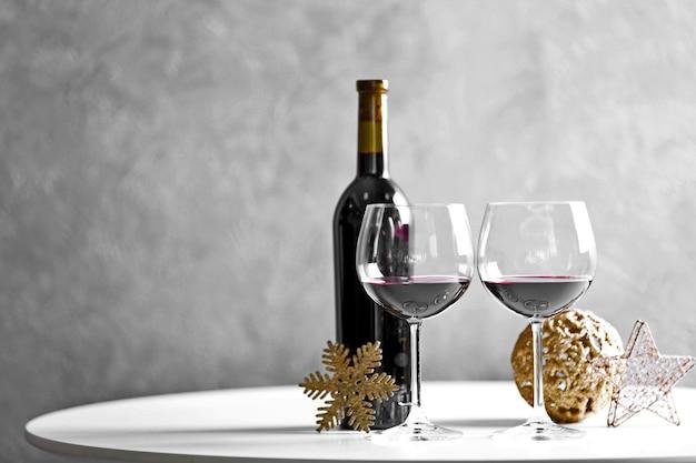 Vin rouge et ornements de noël sur table en bois sur fond de mur