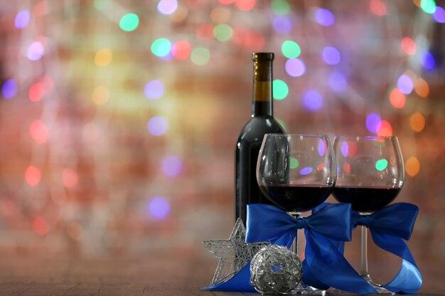 Vin rouge et ornements de noël sur table en bois sur les lumières de noël