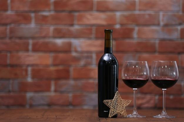 Vin rouge et ornements de noël sur une table en bois sur une surface en brique murale
