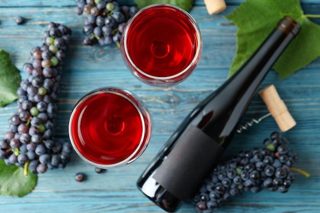 Vin rouge, raisin, liège et tire-bouchon sur table en bois