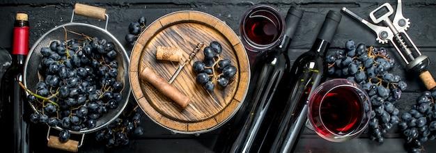 Vin rouge avec des raisins et un vieux tonneau.